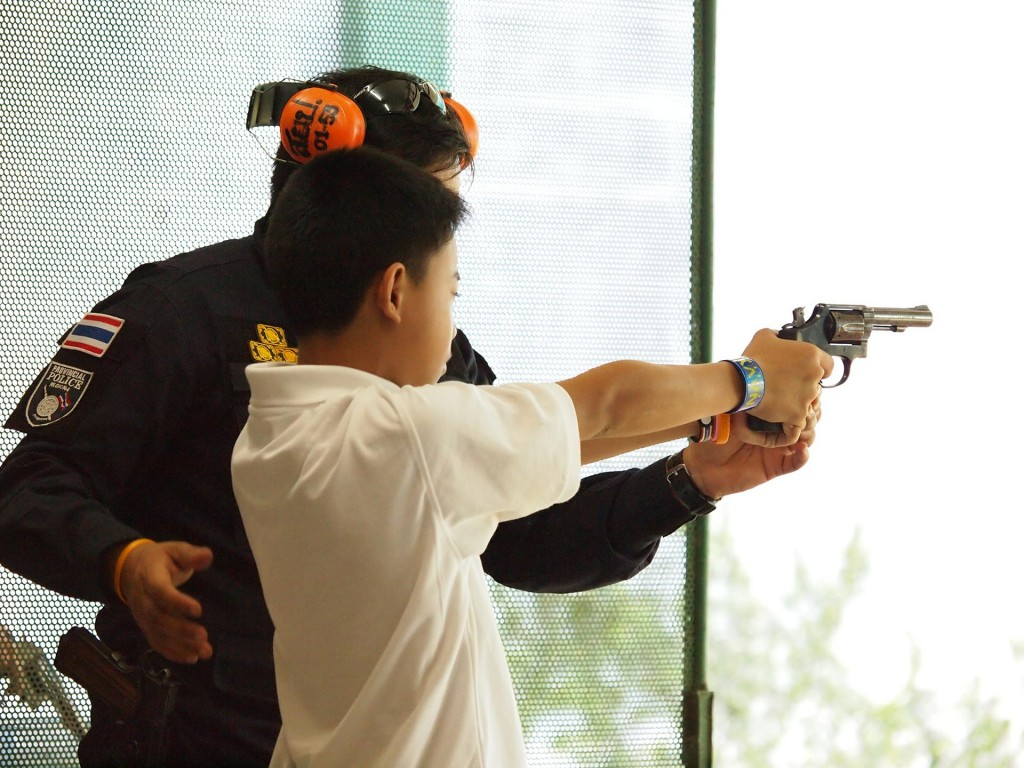 Instructor Teaching a Boy How to Use a Handgun